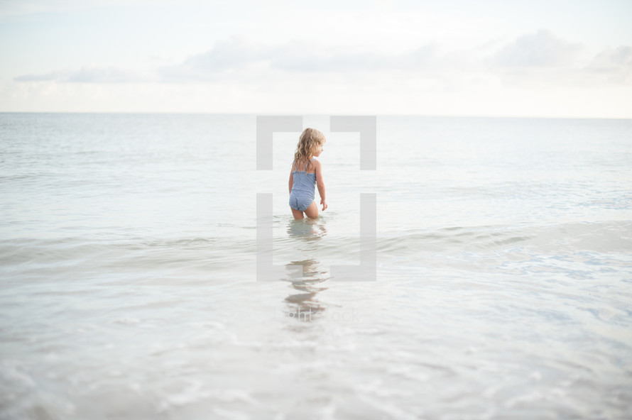 girl child in a bathing suit standing in water