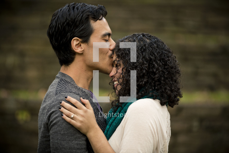 man kissing a woman on the forehead
