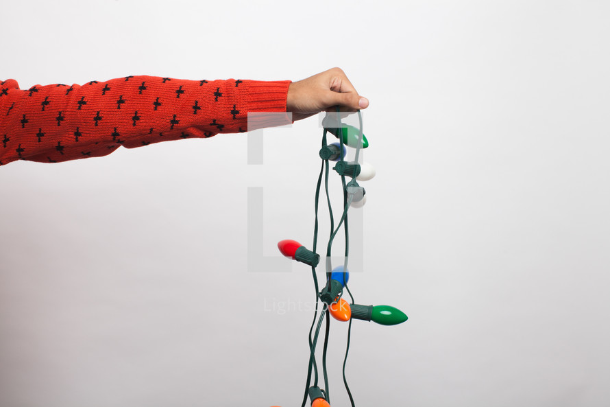 arm holding a strand of Christmas lights