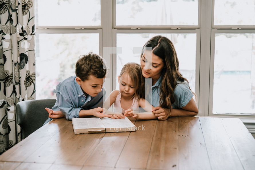 a mother reading a Bible with her kids