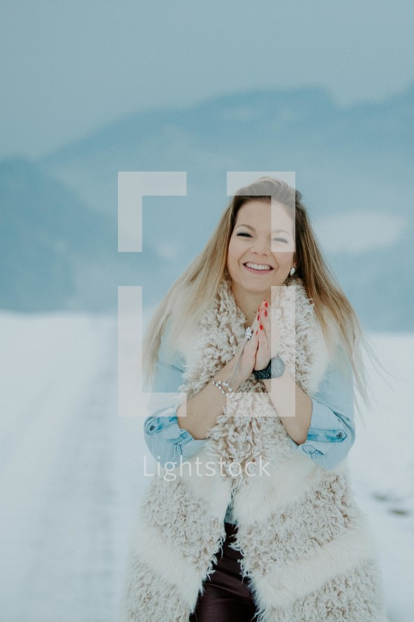 happy woman in a vest standing outdoors in the snow