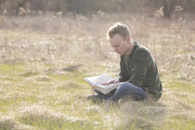 a man sitting in a field reading a Bible