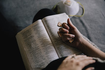 woman holding a cross and praying with a Bible
