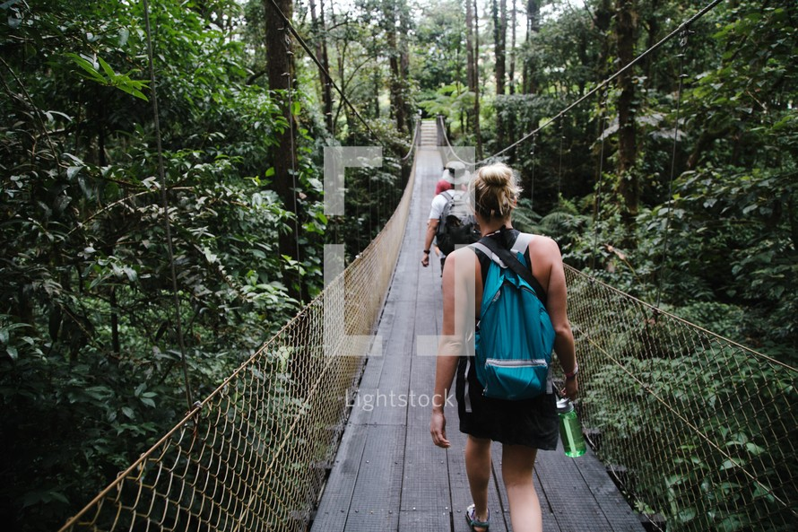 people crossing a swinging bridge in a jungle