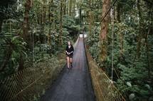 woman walking across a swinging bridge