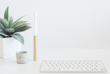A white keyboard, succulent plant and candle on a white surface.