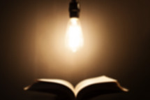 defocused image of an Edison bulb hanging over an open Bible.