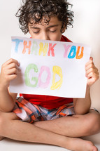 "Boy holding a ""Thank You God"" sign written in crayon."