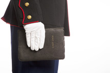 Marine in uniform holding a Holy Bible.