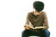 man sitting reading a Bible