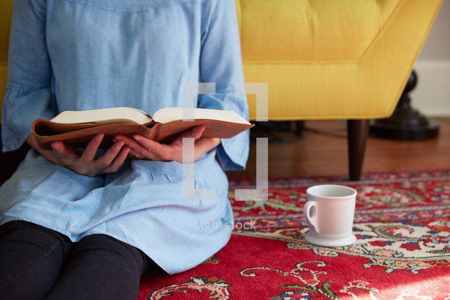 a woman sitting on a floor reading a Bible