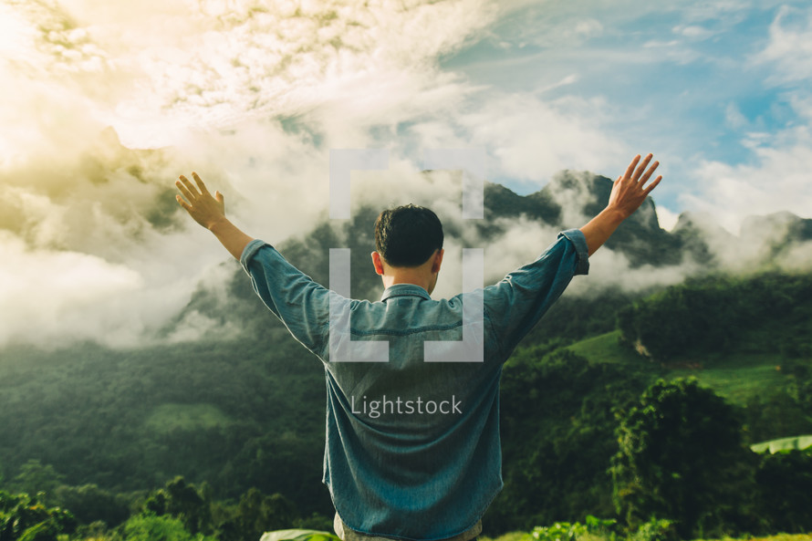 man outdoors with raised hands