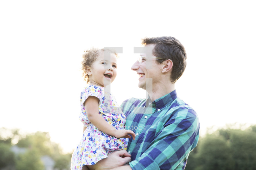 father holding his toddler daughter outdoors