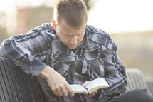 a man in a plaid shirt sitting on a bench outdoors reading a Bible
