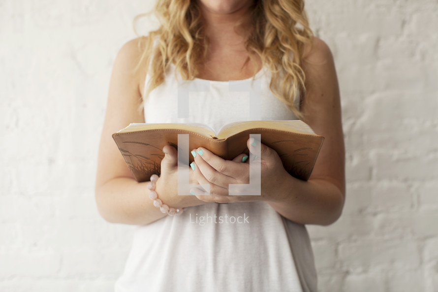 torso of a young woman reading a Bible