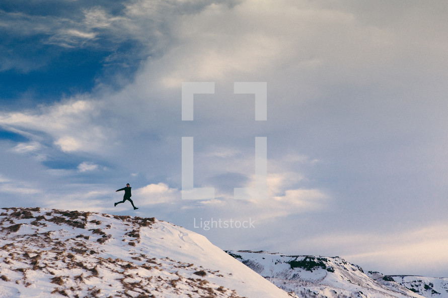 a man leaping on top of a mountain top