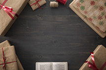 An open Bible surrounded by wrapped gifts.