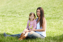 a mother and daughter sitting in the grass