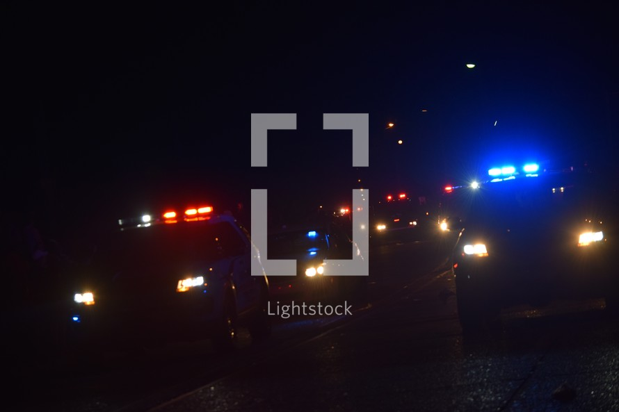 A line of approaching police cars with lights flashing at night