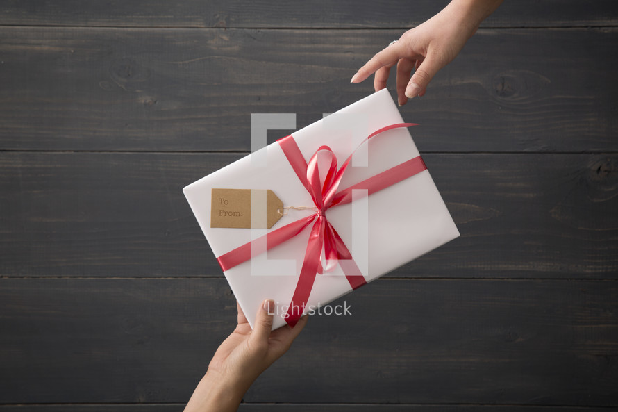 A wrapped gift being given from one person to another.