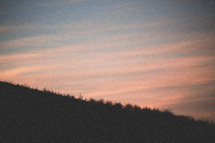 a hill and sky at sunset
