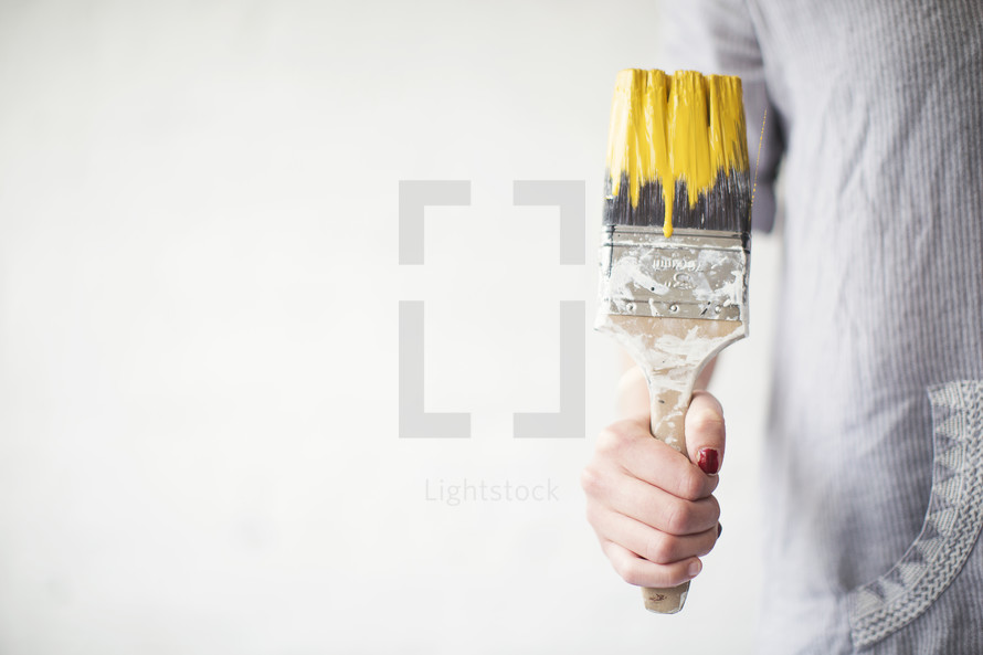 A woman holds a paint brush dripping yellow paint.