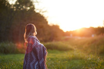 a woman wrapped in a blanket standing outdoors at sunset