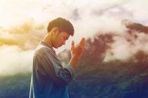 man with raised hands praying outdoors