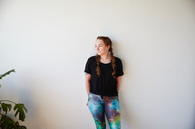 a woman in yoga pants leaning against a white wall