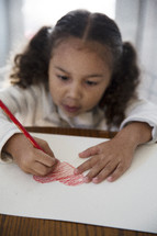 a girl child coloring a heart