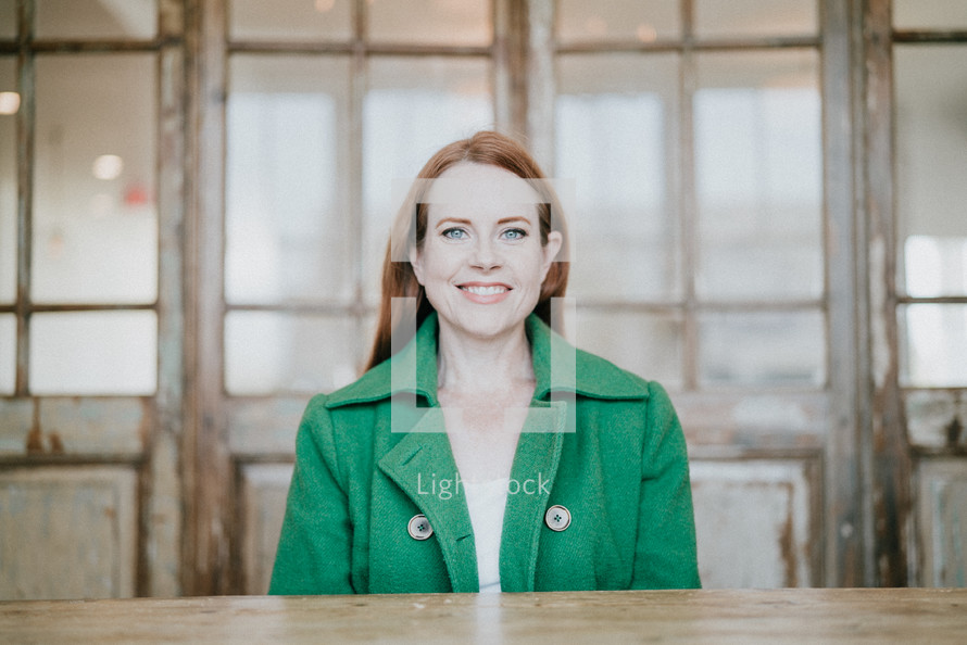 a smiling woman in a green blazer