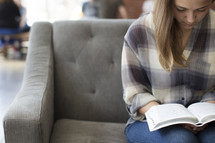 woman sitting on a couch reading a Bible in a coffee shop.