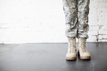 Legs and feet of a female soldier in uniform.