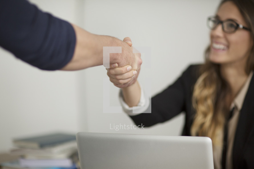 A woman shaking hands with someone.