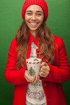 a woman in a red trench coat holding a Christmas mug
