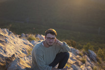 Man sitting on a rocky hill.