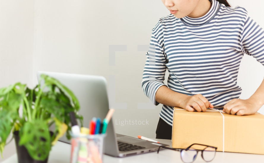 woman wrapping a package looking at a computer screen