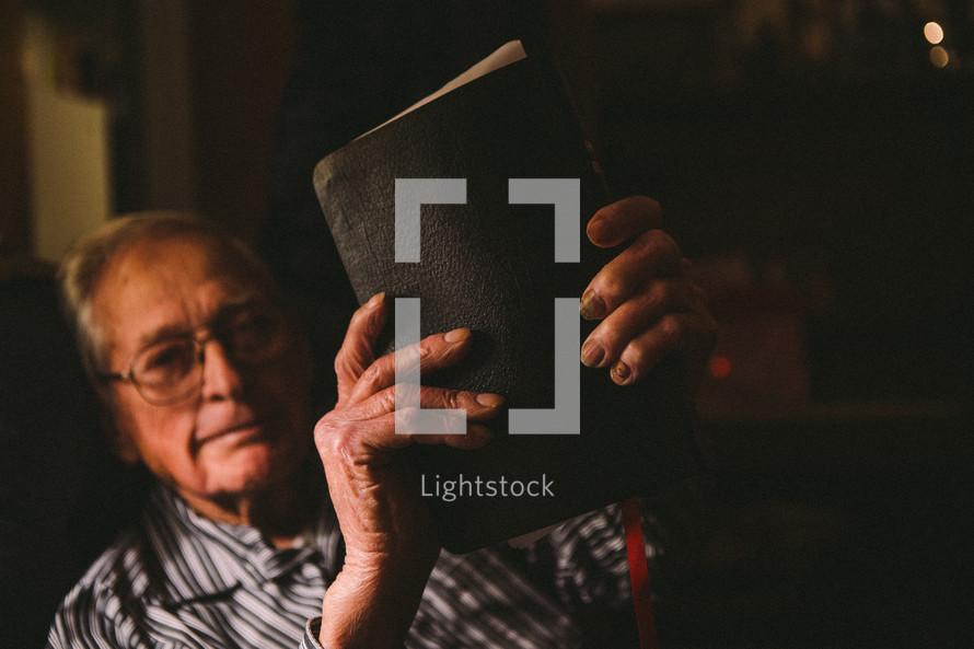 elderly man reading a Bible