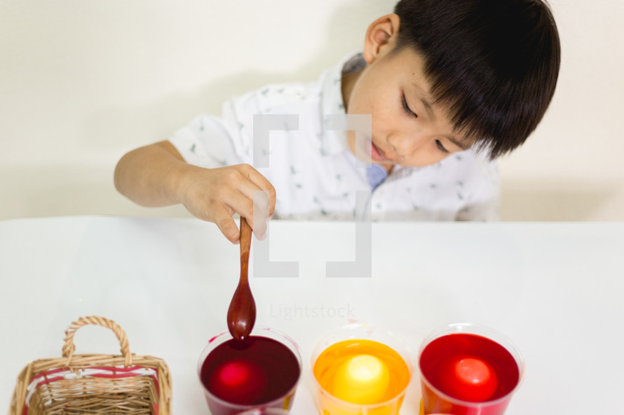 a boy dying Easter eggs