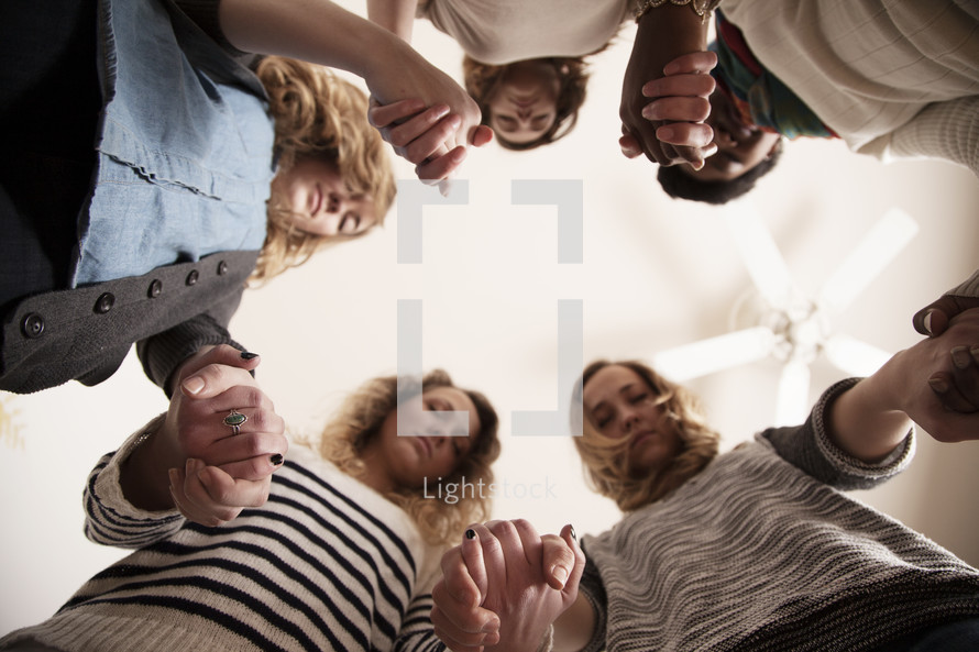 Group of girls holding hands and praying together in a home.