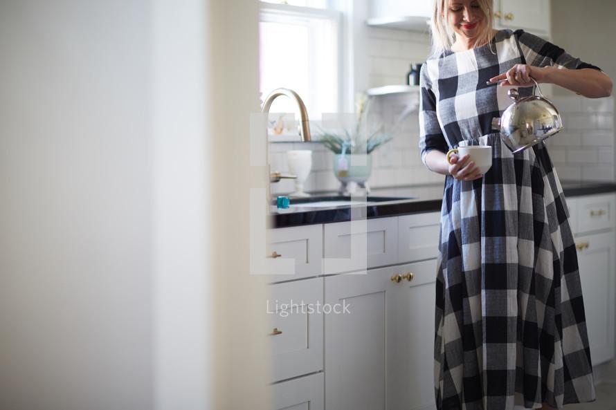 a woman pouring a tea kettle