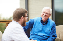 elderly man talking to a young man
