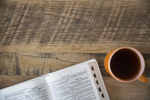 pages of a Bible and coffee mug
