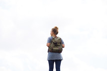 a woman with a backpack standing with her back to the camera.