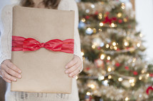 A woman holding a Christmas gift.