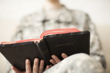 Female soldier in uniform reading the Bible.