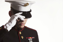 Marine in uniform, adjusting his cover.