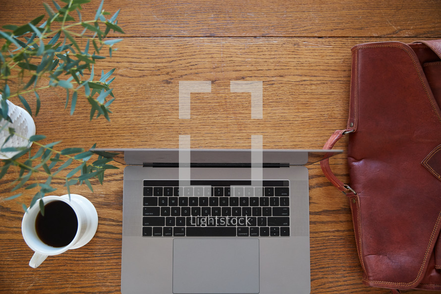 briefcase, laptop computer, coffee cup, and vase of flowers on a desk