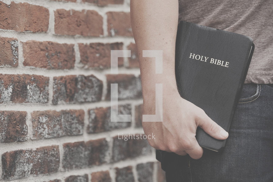 man holding a Holy Bible to his side