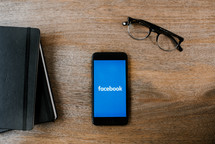 facebook app on a cellphone screen, Bible, and journal